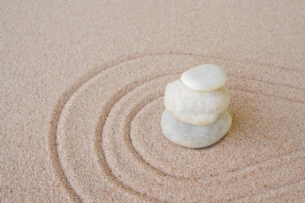 Zen garden stone japanese on raked sand. rock or pebbles on beach design outdoor for meditate peace of mind and relax. chan buddhism religion concept.