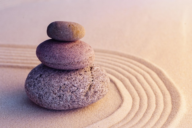 Zen garden stones on sand with ornament copy space