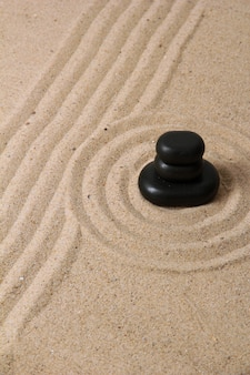 레이크 모래와 둥근 돌이있는 젠 가든을 닫습니다.