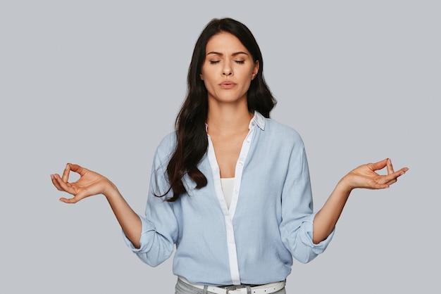 禅のような。灰色の背景に立っている間瞑想し、目を閉じておく魅力的な若い女性