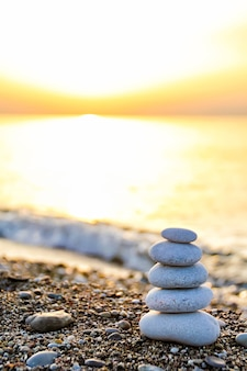 日の出の浜辺にある禅のような石のピラミッド