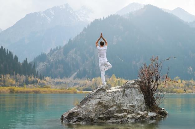 A zen man in white practices yoga in nature. pose vrikshasana or tree pose.