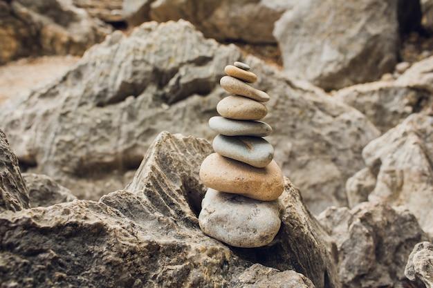 Релаксация медитации дзэн - винтажное ретро-эффект отфильтровывает изображение стиля битника сбалансированного стога камней с концом цветка plumeria frangipani вверх на пляже моря.
