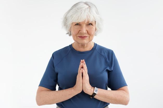 禅、リラクゼーション、引退、瞑想。愛らしいエネルギッシュな中年女性年金受給者がヨガを練習し、ナマステのジェスチャーで手をつないで、太陽礼拝シーケンスを行います