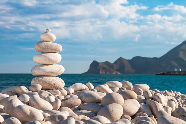 Дзен рок-пирамида из белой гальки на камнях пляжа.