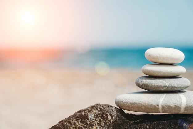 禅の石は、空の海とビーチを背景にした小石のピラミッドの背景です...