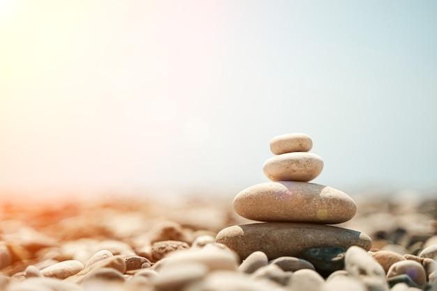 禅の石は、空の海とビーチを背景に小石のピラミッドを背景にしています