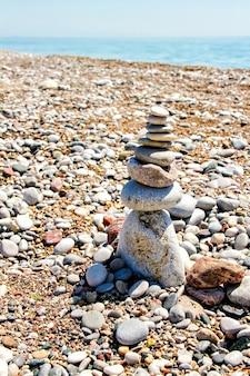 Камни дзен сложены на пляже на фоне гравия, неба и моря