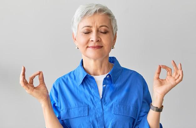 禅、知恵、バランス、リラクゼーションのコンセプト。ムードラジェスチャーで親指と人差し指を接続するヨガの後に瞑想を閉じて目を閉じてポーズをとる50代の美しい白髪の女性