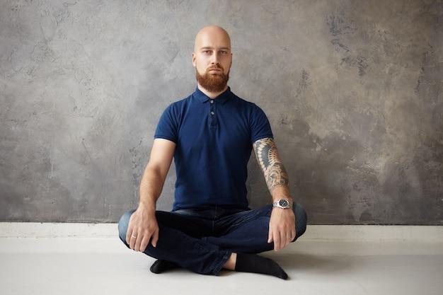 Concetto di zen, yoga e meditazione. colpo isolato del bel ragazzo barbuto con la testa rasata seduto sul pavimento di legno con le gambe incrociate, avendo calma espressione facciale, meditando con gli occhi aperti
