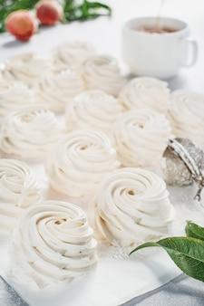 Зефир десерт крупным планом, выборочный фокус, посыпанный сахарной пудрой. идея сделать зефир из персикового пюре с добавлением агара. фон белой бумаги. время чая