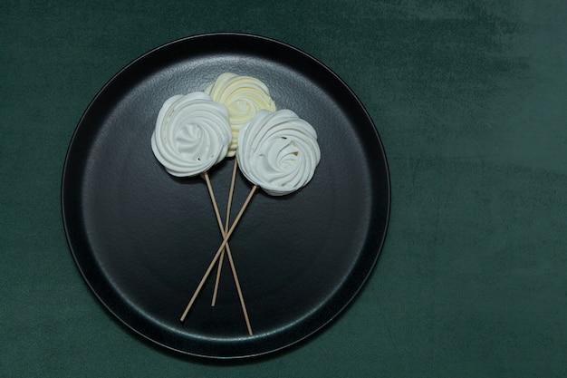 黒いプレートにゼファーまたはマシュマロ。バレンタインや母の日のスティックやオリジナルの甘い花束の美しいメレンゲ。