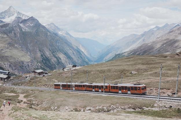 체르마트, 스위스 - 2017년 6월 24일: 관광객을 태운 고르너그라트 기차가 스위스, 스위스, 유럽 국립공원의 마터호른 산으로 갈 것입니다. 여름 풍경 anddramatic 푸른 하늘