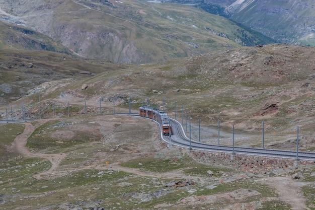 체르마트, 스위스 - 2017년 6월 24일: 관광객을 태운 고르너그라트 기차가 스위스, 스위스, 유럽 국립공원의 마터호른 산으로 갈 것입니다. 여름 풍경, 햇살 날씨, 극적인 푸른 하늘