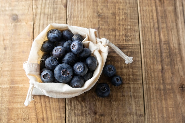 Zero waist concept. blueberries spilling out of a brown textile, eco bag over rustic wood table.