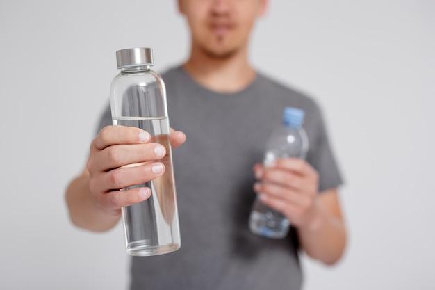 ゼロウェイストと環境にやさしいコンセプト-灰色の背景の上に再利用可能なガラスとペットボトルの水を比較する若い男
