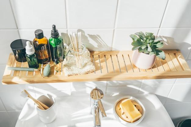 バスルームの白い壁に竹や再利用可能な化粧品やトイレタリーを無駄にしない。有機コスメティス。ウェルネスと持続可能性の概念