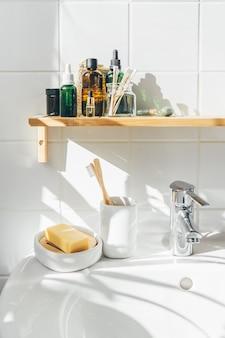 モダンな白いバスルームで、無駄のない竹と再利用可能な化粧品とトイレタリー。有機コスメティス。ウェルネスと持続可能性の概念。壁の影