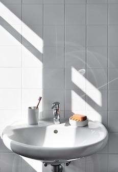 Zero waste bathroom items such as glass mug, bamboo toothbrush, organic soap