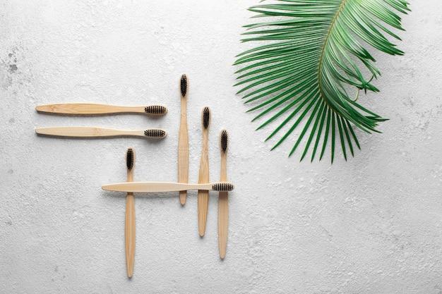 Нулевые отходы, биоразлагаемая бамбуковая зубная щетка на серой каменной бетонной столешнице с зеленым пальмовым листом сбоку. концепция спасения планеты, экология, эко