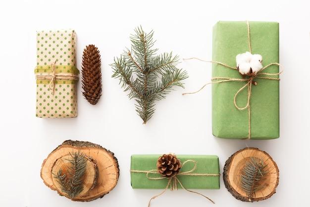 Нулевой отход рождественской композиции фон из сосновых шишек, ветвей, свечей, годичных колец, созданных подарков без пластика на белом столе. вид сверху, крупным планом, копией пространства, фон, плоская планировка.