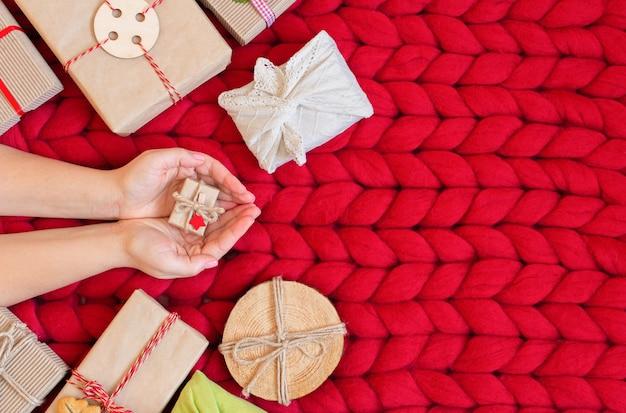 ゼロウェイストクリスマスフラットレイ。柔らかな手編みのメリノウールの毛布に素朴なスタイルのクラフト紙でクリスマスプレゼントを持っている手。プラスチックフリー。エコ装飾コンセプト。