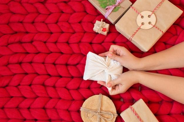 ゼロウェイストクリスマスフラットレイ。柔らかい手編みのメリノウールの毛布に伝統的な日本の風呂敷風のリネン生地でクリスマスプレゼントを持っている女性の手。プラスチックフリー。エコ装飾コンセプト。