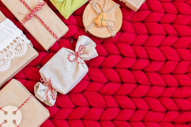 Zero waste christmas gift boxes on a soft hand knitted merino wool blanket  hand crafted gifts with natural xmas decorationsw rapping craft paper without plastic