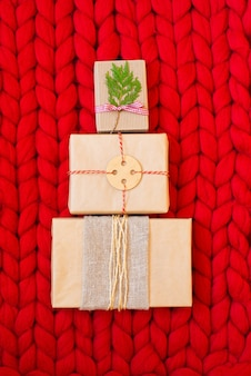 柔らかい手編みのメリノウールの毛布に対してクリスマスツリーの形をしたプラスチックを含まないクラフト紙で包まれた、自然なクリスマスの装飾が施された無駄のないクリスマスギフトボックス。エコデコレーションコンセプト。