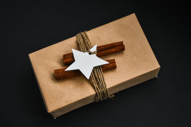 제로 웨이스트 크리스마스는 검정색 배경에 장식이 있는 선물입니다. 공간을 복사합니다. 공예 판지로 만든 태그가 있는 친환경 포장된 선물. 새해