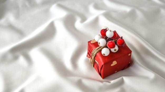 제로 웨이스트 크리스마스 선물은 샴페인 색 실크 배경에 장식되어 있습니다. 공간을 복사합니다. 공예 판지로 만든 태그가 있는 친환경 포장된 선물. 새해