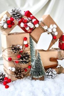 제로 웨이스트 크리스마스 선물은 샴페인 색 실크 배경에 장식되어 있습니다. 공간을 복사합니다. 공예 판지로 만든 태그가 있는 친환경 포장 선물. 새해