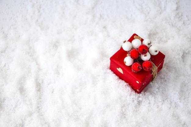 제로 폐기물 크리스마스 선물은 하얀 눈 배경에 장식되어 있습니다. 공간을 복사합니다. 공예 판지로 만든 태그가 있는 친환경 포장된 선물. 새해