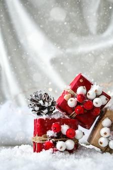 제로 폐기물 크리스마스 선물은 하얀 눈 배경에 장식되어 있습니다. 공간을 복사합니다. 공예 판지로 만든 태그가 있는 친환경 포장 선물. 새해