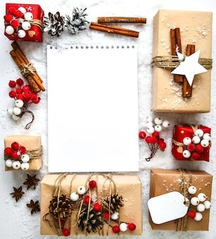 하얀 눈 배경에 장식이 있는 선물이 있는 크리스마스 텍스트 낭비가 없습니다. 노트북 빈 복사 공간입니다. 공예 판지로 만든 태그가 있는 친환경 포장된 선물. 새해