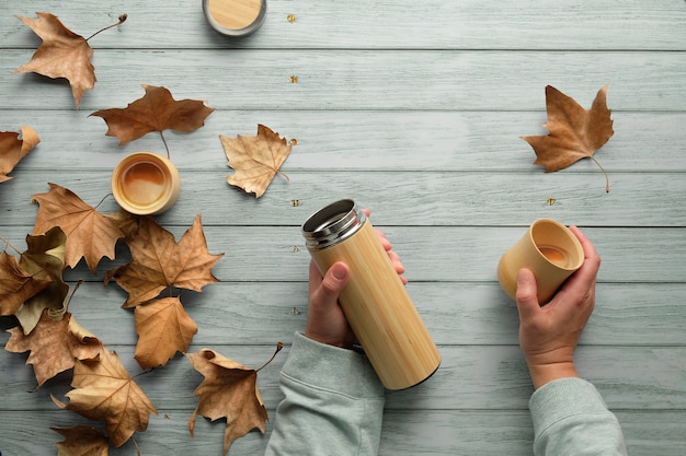 Zero waste coffee in bamboo cups from eco friendly insulated metal flask in fall. hands holding the flask and cup.