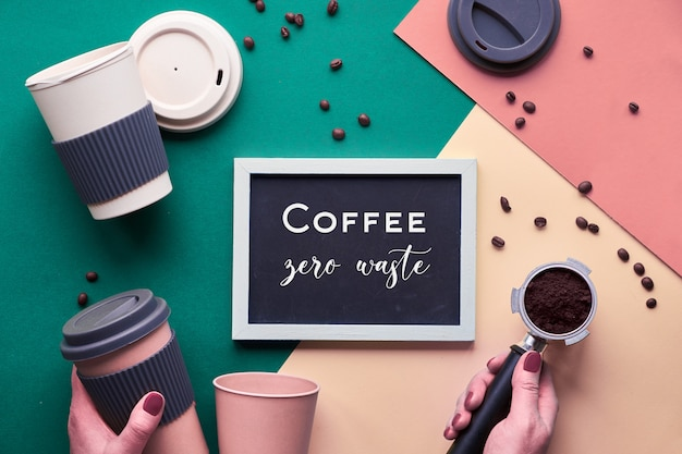 Zero waste coffee concept. eco friendly reusable coffee cups in hands, geometric flat lay on split paper, beige and yellow with white chalk text on black board.