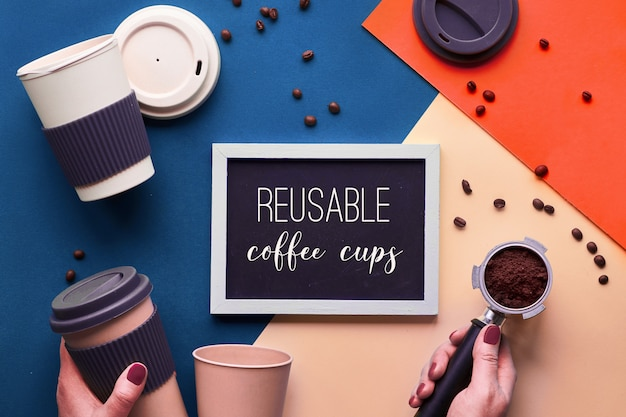 Zero waste coffee . eco friendly reusable coffee cups in hands, geometric top view on split paper in classic blue, cream and luish lava color tones with copy-space on blackboard.