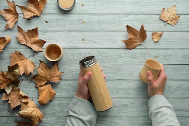 秋の環境にやさしい断熱金属フラスコからの竹製カップに入った無駄のないコーヒー。フラスコとカップを保持している手。