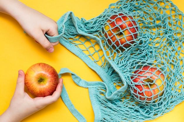 Ноль отходов концепции. детские руки складывают спелые яблоки в хлопковую сетчатую сумку. вид сверху.