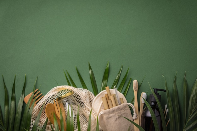 Zero waste concept. cotton bag, bamboo cultery, glass jar, bamboo toothbrushes, hairbrush and straws on green background
