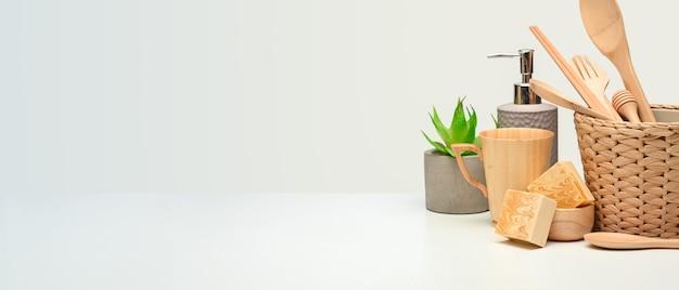 ゼロウェイストのコンセプト、木製の台所用品、植木鉢、白いテーブルのコピースペースのあるクリエイティブなシーンをクローズアップ