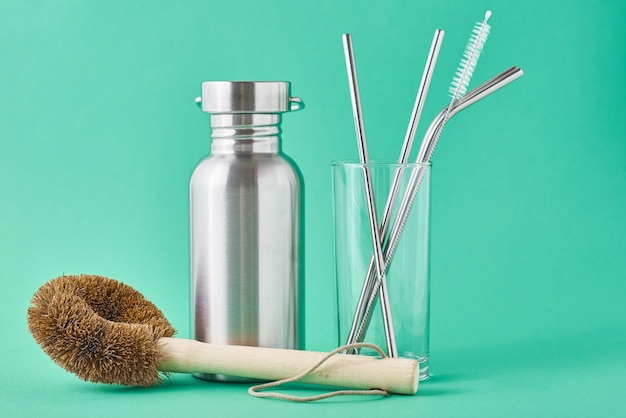Zero waste concept. eco friendly reusable items aluminum bottle and metal tubes in glass on green wall