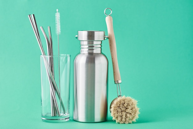 Zero waste concept. eco friendly reusable items aluminun bottle and metal tubes in glass on green