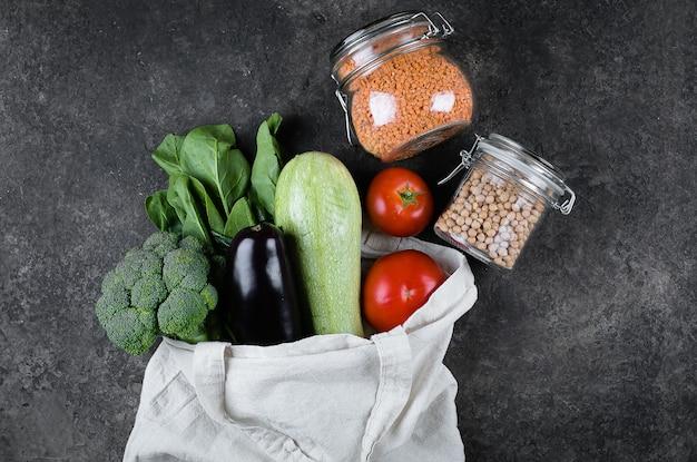Zero waste concept. female hands holding vegetables, reusable bag, glass jars hickpea, lentils