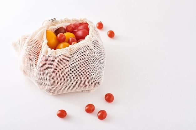 ゼロウェイストのコンセプト。白い背景の上のテキスタイルバッグの新鮮な有機野菜。