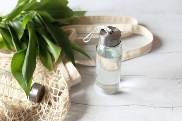 ゼロウェイストのコンセプト。白い木製のテーブルの上のガラスの水筒とエコバッグ。