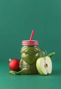 Zero waste concept. green apple spinach smoothie on green background in glass santa claus jar. healthy and diet food concept