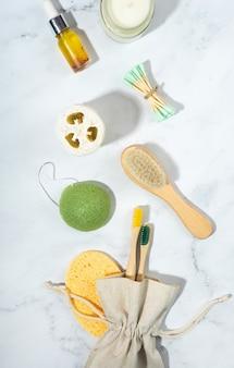 제로 폐기물 개념.린넨 가방, 대나무 칫솔, 나무 귀 스틱, 유리에 소이 왁스 양초. 유행 그림자, 흰색 배경입니다. 수세미 수건.친환경, 지속 가능한 생활 방식. 조롱