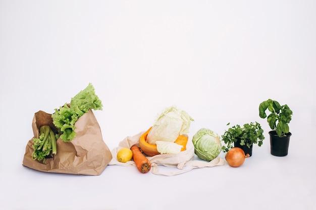 ゼロウェイストのコンセプト。パッケージフリーのフードショッピング。有機果物と野菜が入った環境にやさしいナチュラルバッグ。持続可能なライフスタイルのコンセプト。プラスチックフリーのアイテム。再利用、削減、拒否します。白で隔離